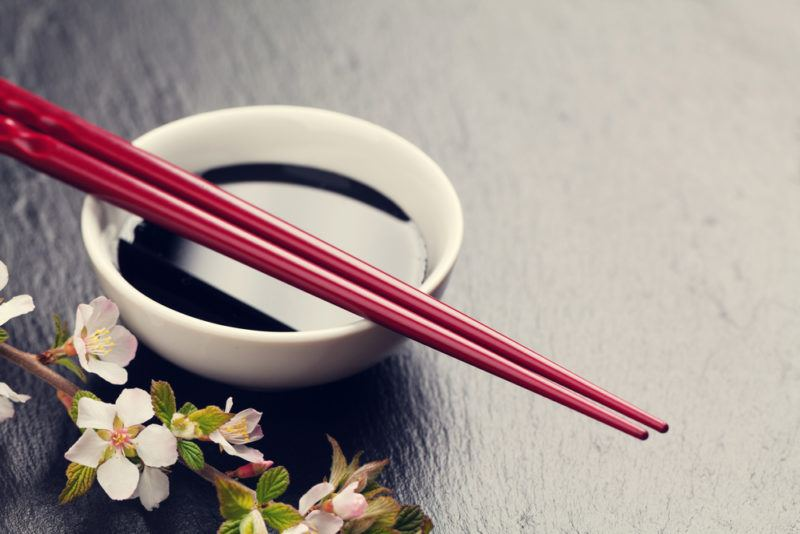 A small white bowl that contains soy sauce, with two chopsticks next to white flowers