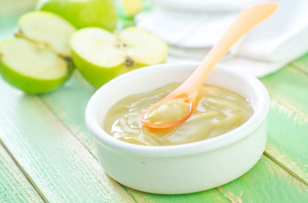 A white bowl of apple baby food on a green table, next to some green apples in halves