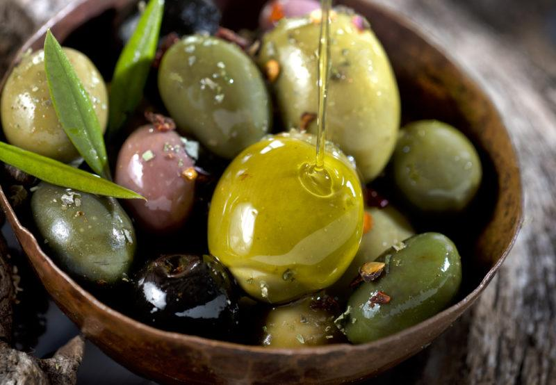 A small brown bowl that contains fresh olives with olive oil being drizzled over them