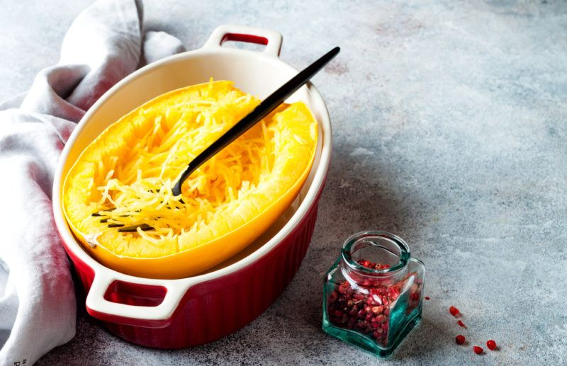 A red dish with a cooked spaghetti sqash and a spoon or fork