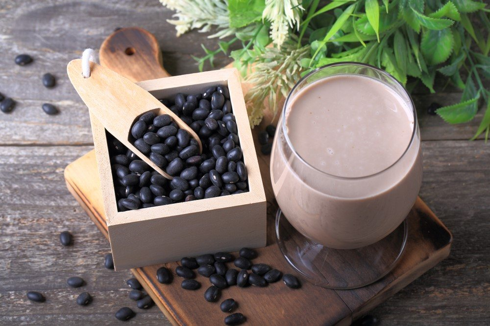 A square box with black soybeans and a glass of black soybean milk