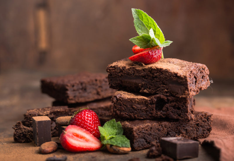 A stack of chocoalte brownies, with some strawberries and mint leaves