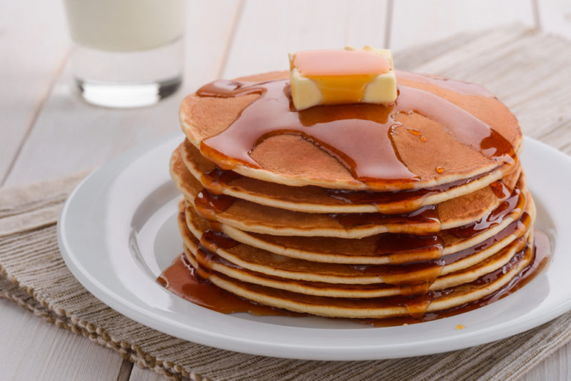 A stack of pancakes on a white plate with a knob of butter on top and maple syrup running down the sides