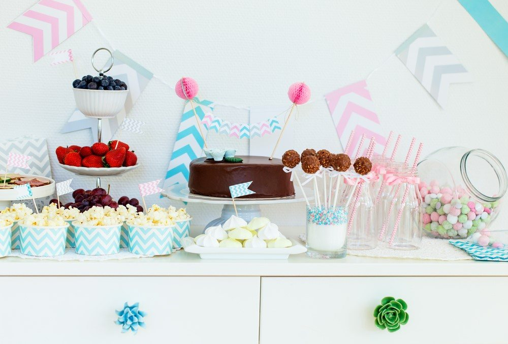 A table with baby shower snacks and decorations