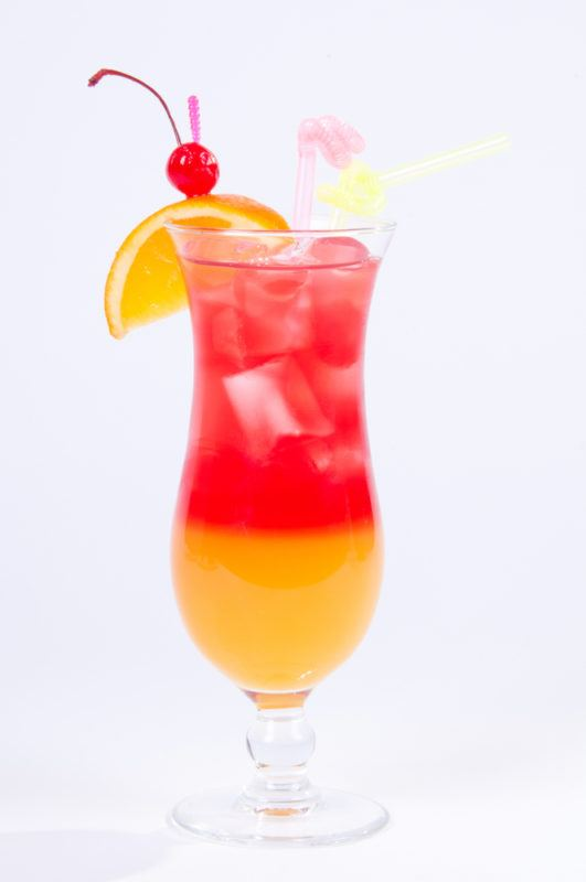 A tequila sunset cocktail in a tall glass isolated on white