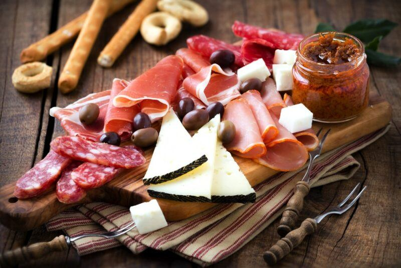 A wooden table with various Spanish tapas, including cheese and cured meat
