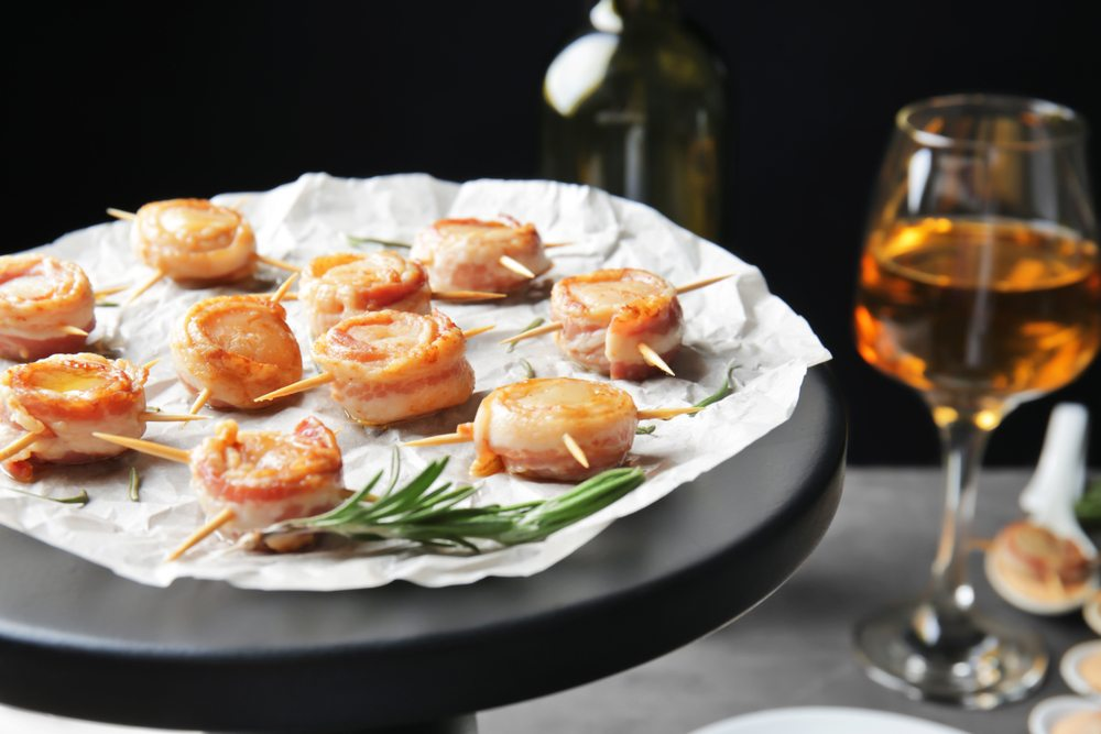 A platter with bacon wrapped scallops next to a glass of wine
