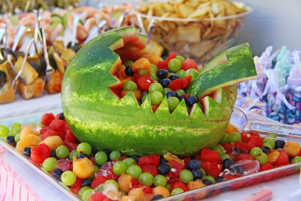 A tray with fruit salad that relies on melon balls, along with a baby carriage made from a watermelon
