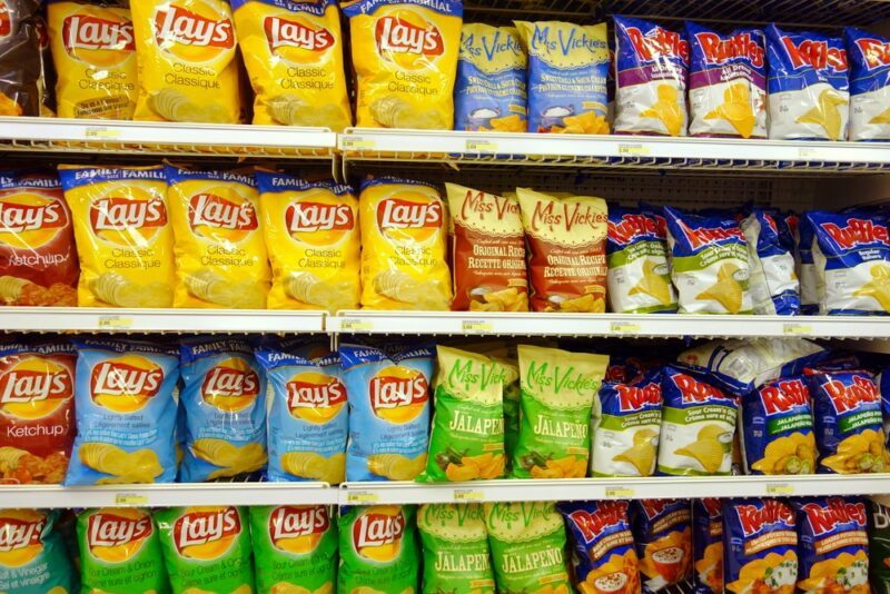 Four shelves in the grocery store, filled with chips