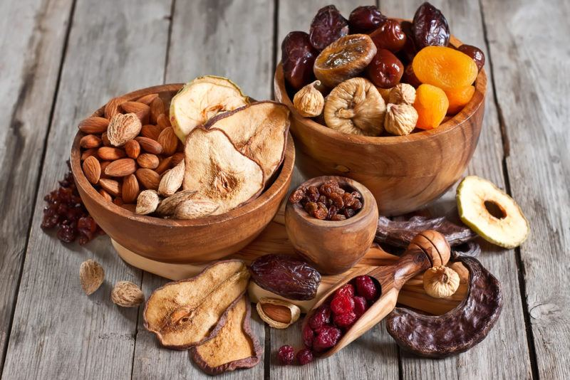 Three wooden bowls of various sizes filled with dried fruit and almonds, with more dried fruit on the table