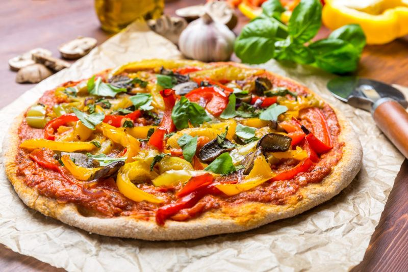 A vegan pizza with many vegetables on a cloth on a table
