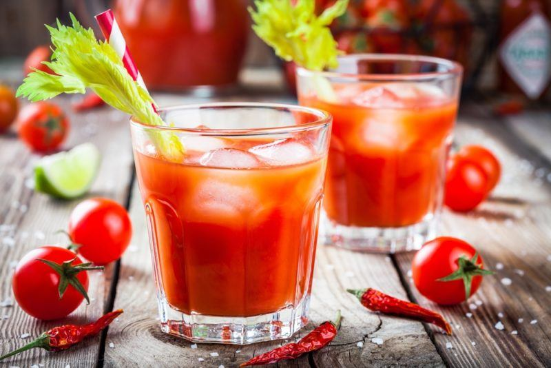 Two glasses of virgin bloody Mary on a wooden table with cherry tomatoes and peppers scattered around