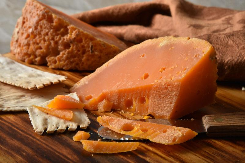 A wedge of gourmet Mimolette french cheese and artisan crackers