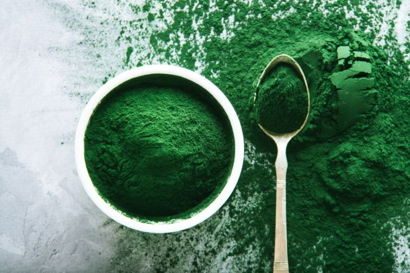 A flat lay image of a white bowl containing spirulina powder, spirulina powder on a spoon and the same powder scattered across a table