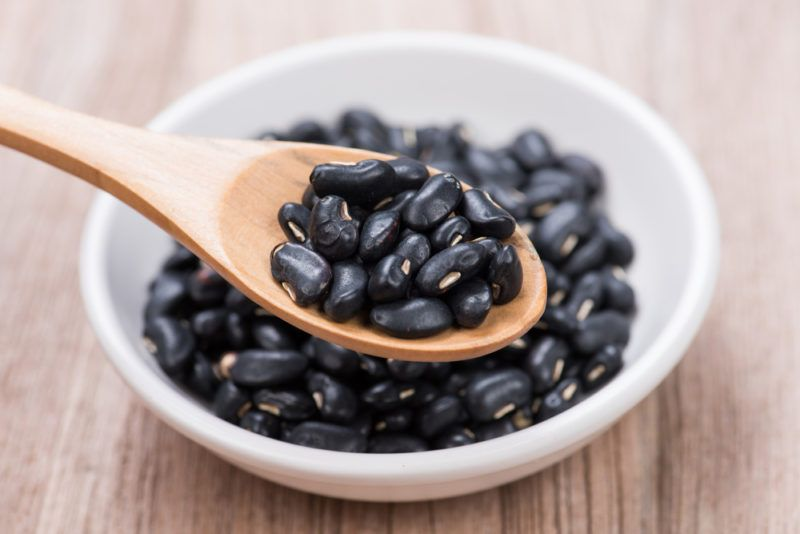 A white bowl containing black beans with a spoon