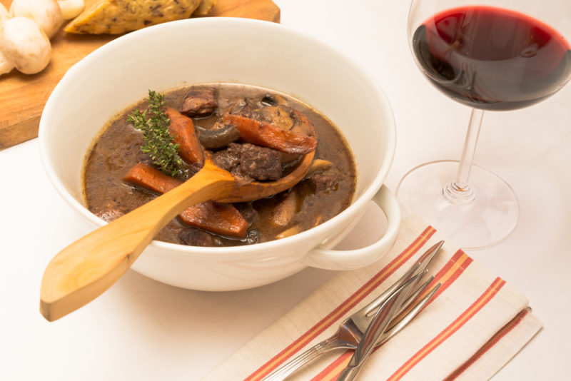 A white bowl with a handle filled with beef stew next to a glass of red wine