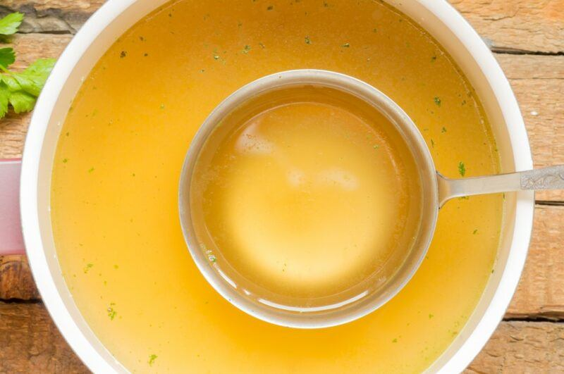 A large white bowl of clear bone broth, with a ladel in it