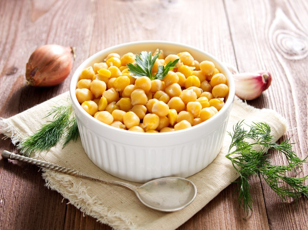 A white bowl containing cooked chickpeas next to a spoon and some herbs