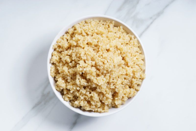 A white bowl containing cooked quinoa on a marble background