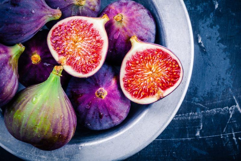 A white bowl with fresh figs. One has been sliced in half, showing the bright flesh