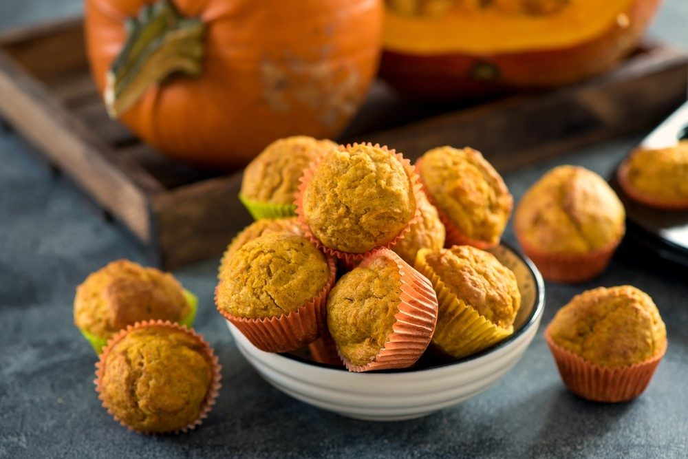 A small bowl of tiny muffins with a few scattered on the table, in front of a pumpkin