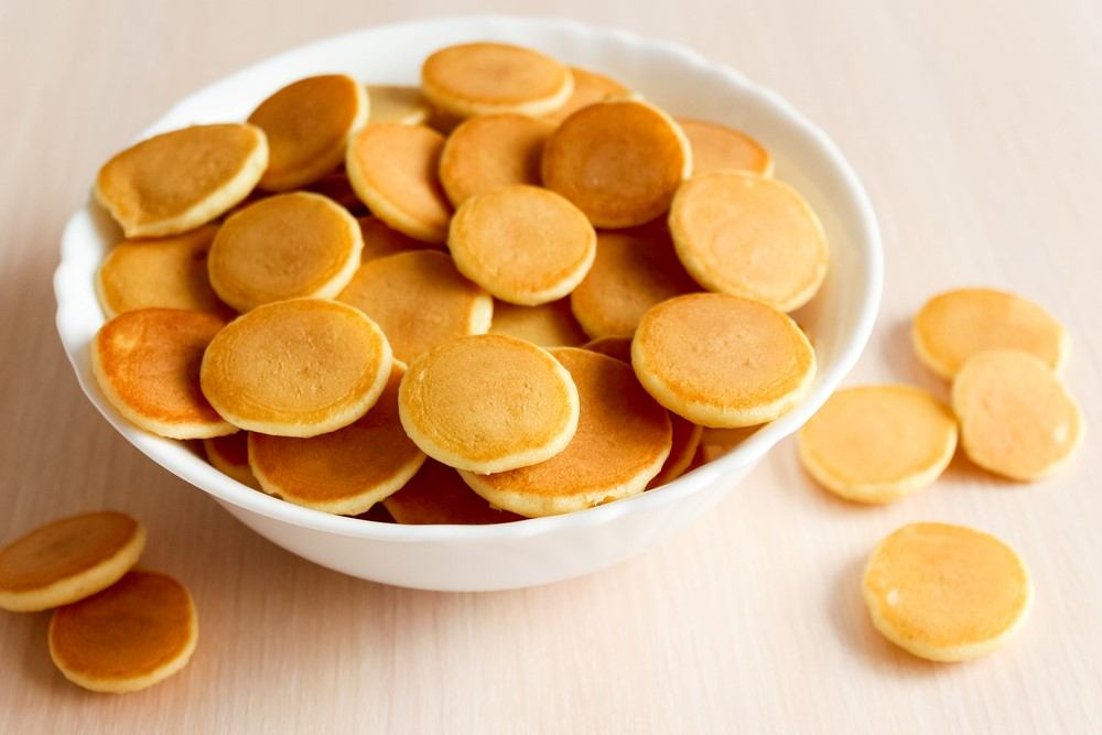 A white bowl with tiny pancakes and a few pancakes on the table