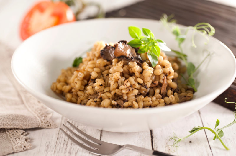 A white bowl that contains mushroom risotto next to a fork
