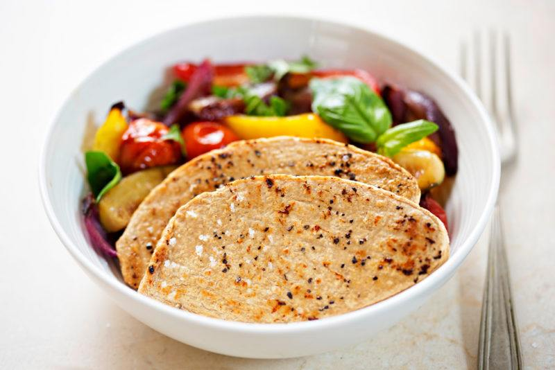 A white bowl that contains a few slices of cooked quorn, along with variouvegetables