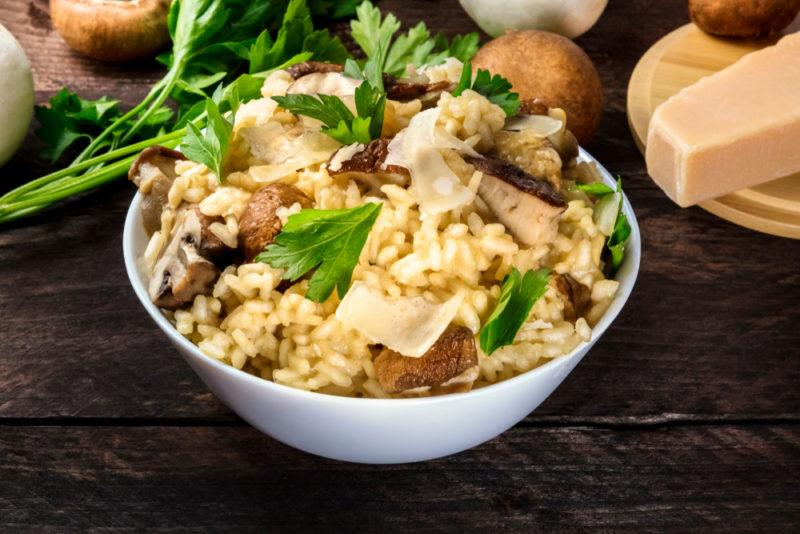 A white bowl of rice risotto with some greens on top, mushrooms, and parmesan cheese