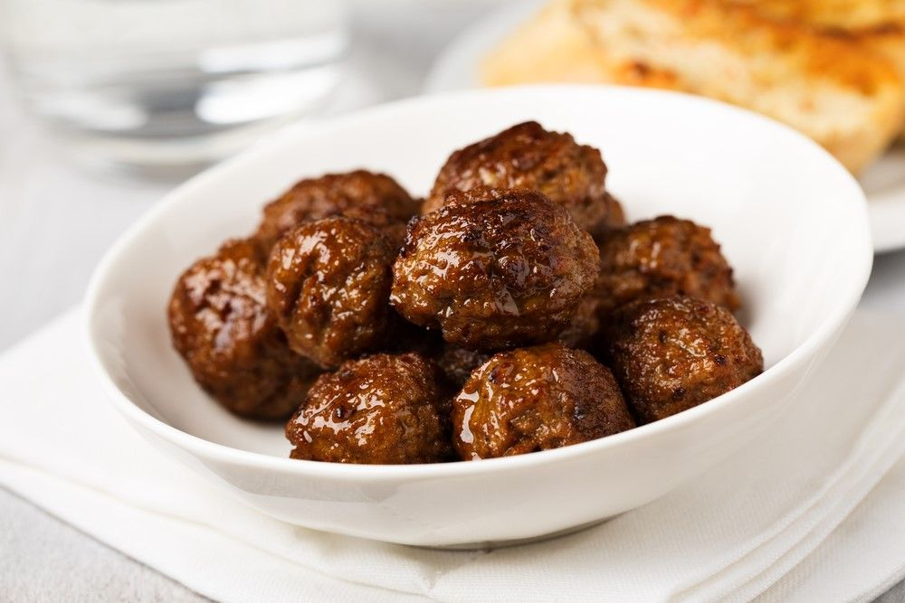 A small white bowl of meatballs
