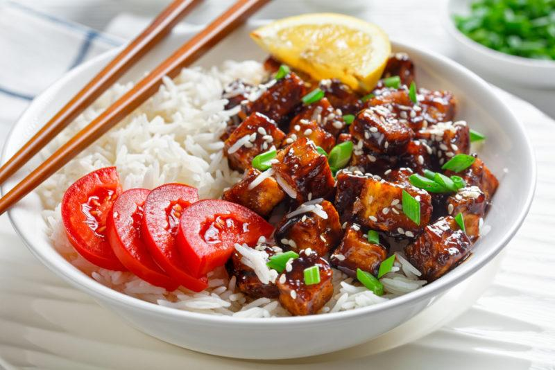 A white bowl filled with rice, marinated tofu, sliced tomatoes, with chopsticks