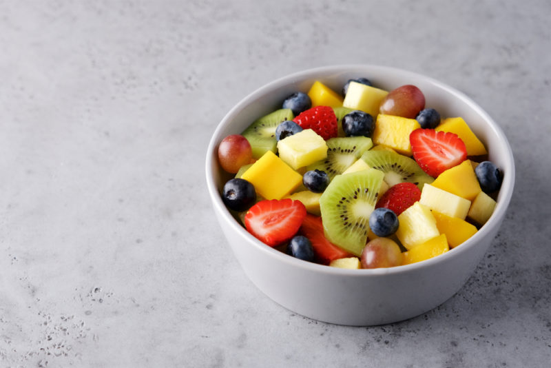 A white bowl on a marble table that contains fruit salad