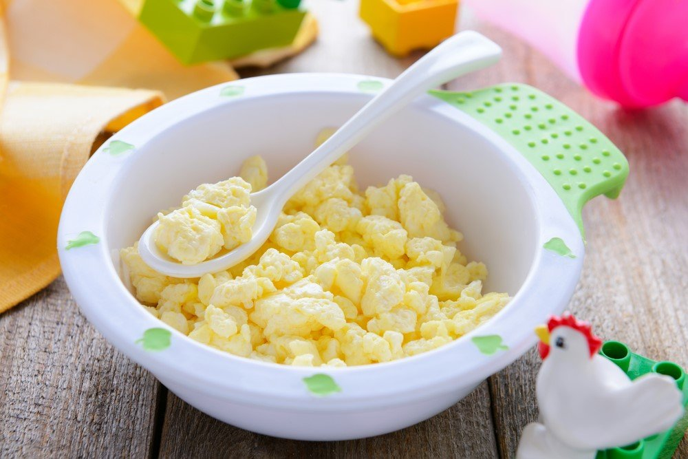A white and green bowl of scrambled eggs