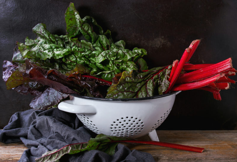 A white colander filled with dark leafy greens, including Swiss chard