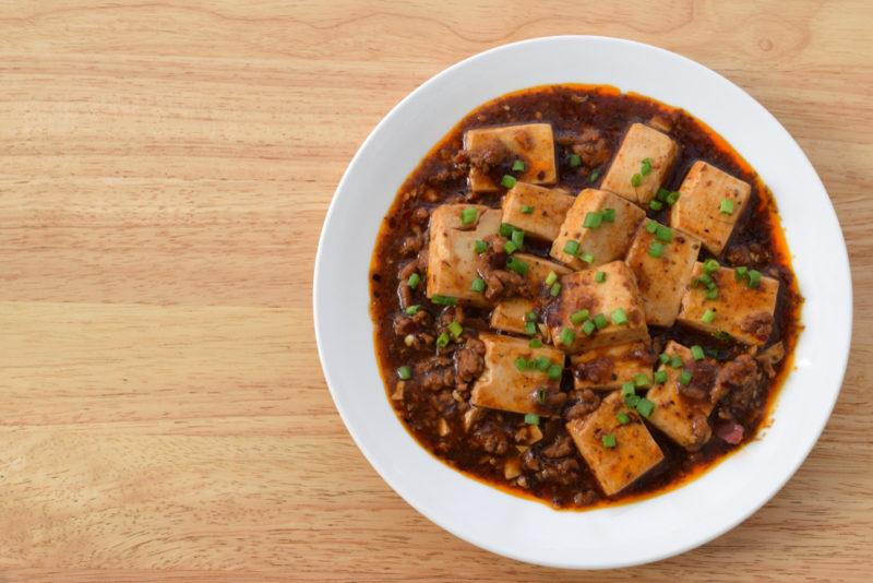 A white bowl on a light wooden table that contains ma po tofu