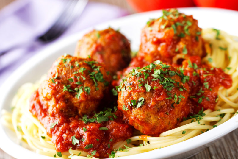 A white dish of meatballs on cooked spaghetti