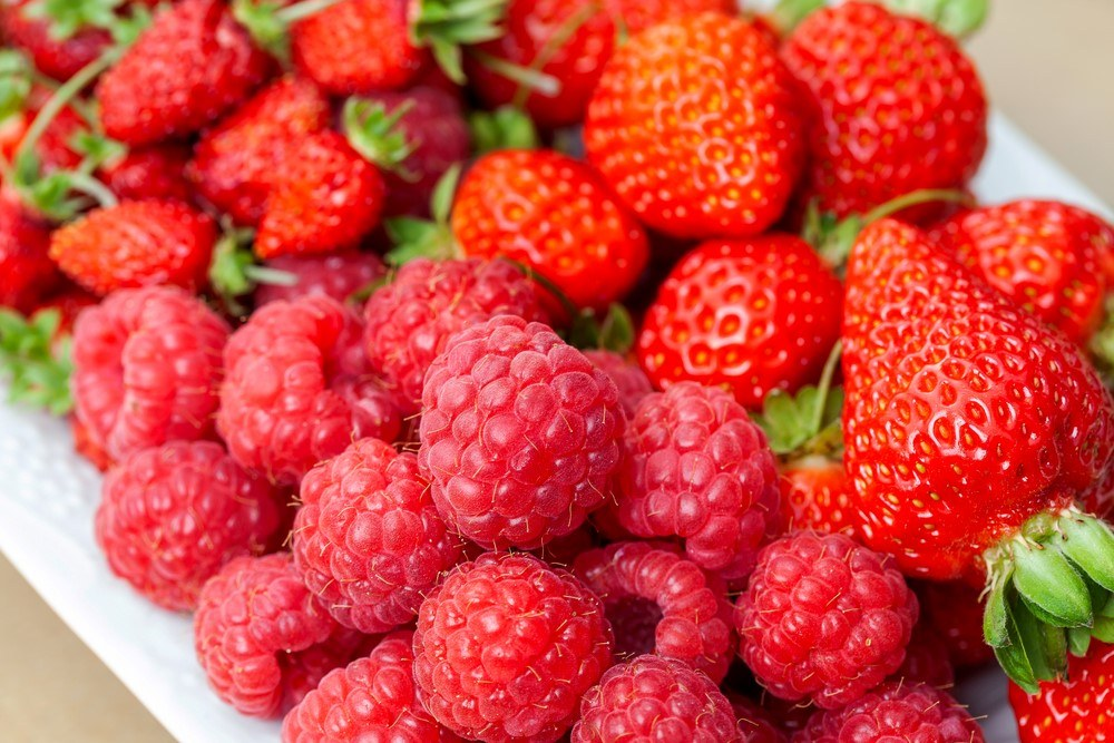A white dish that includes strawberries, wild strawberries, and raspberries