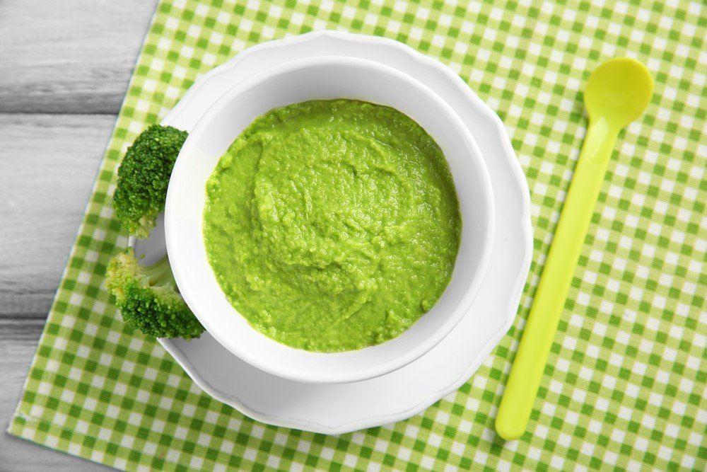 A white plate and a white bowl filled with broccoli or zucchini puree