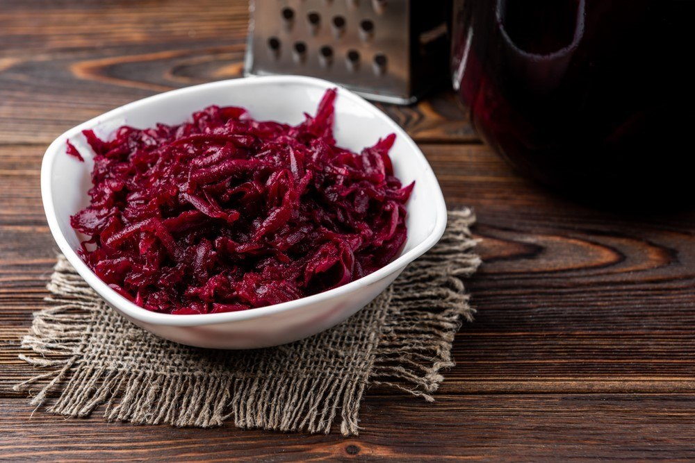 A white bowl with cooked shredded beets in front of a grater