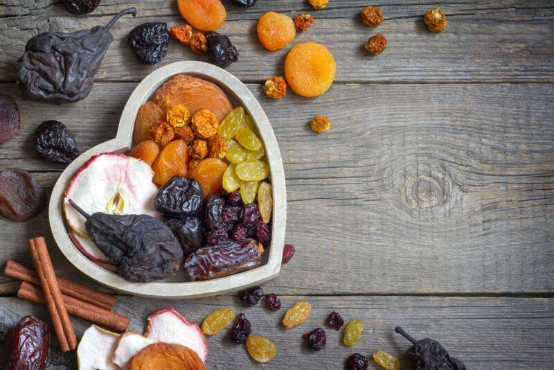 A wooden table with a white heart that's filled with dried fruit and other pieces of dried fruit scattered across the table