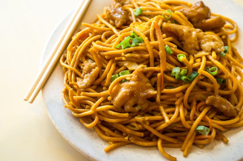 A white plate with chopsticks and lo mein