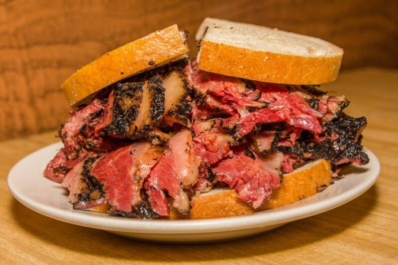 A white plate with a large sandwich made using hot pastrami