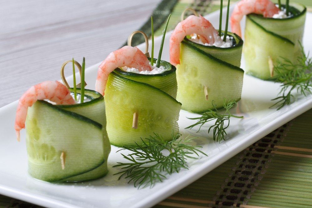 A white plate that contains four appetizers made from cucumber, filled with cream cheese and a prawn