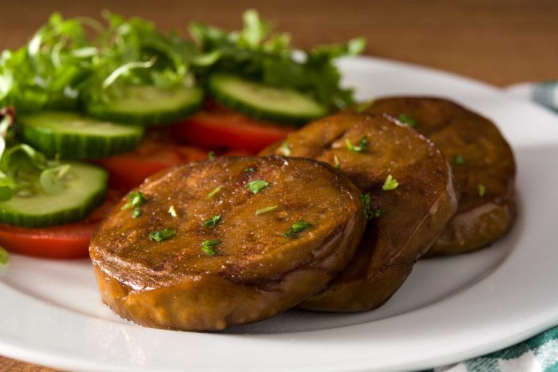 A white plate with tomatoes and cucumber, along with marinated and sliced seitan