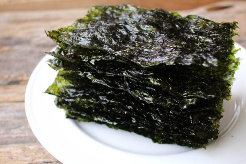 A white plate with a stack of seaweed snacks