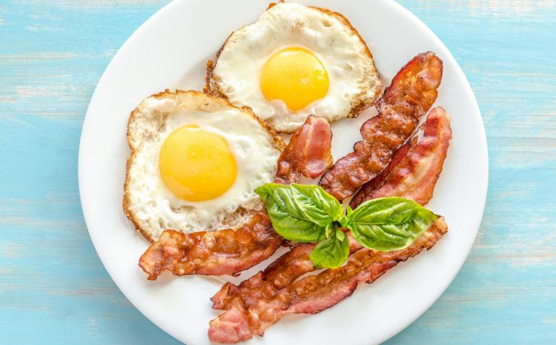 A white plate with two fried eggs, some strips of bacon and greens
