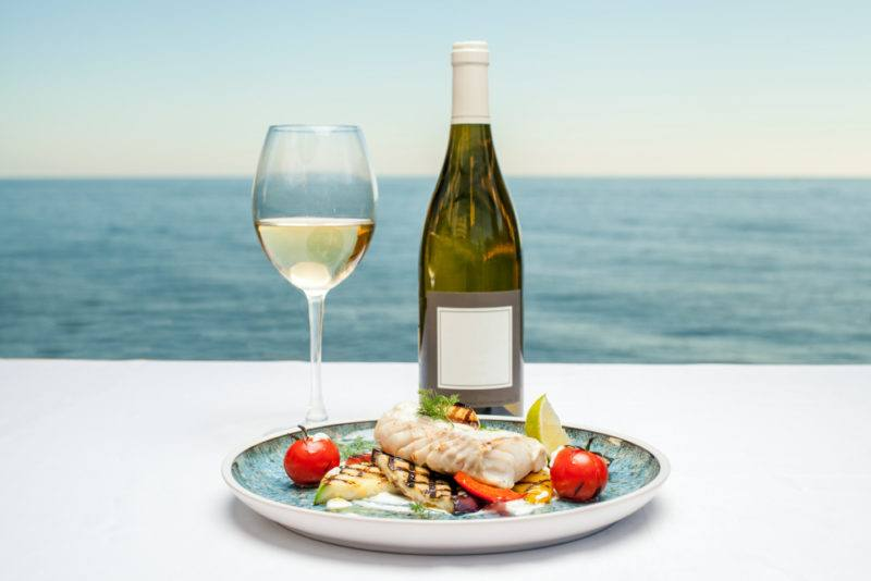 A glass of white wine and a bottle of wine next to a dish of cooked fish in front of the ocean