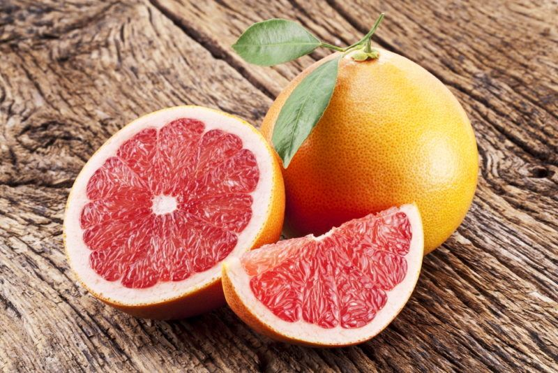 A whole pink grapefruilt, half a pink a grapefruit and a quarter