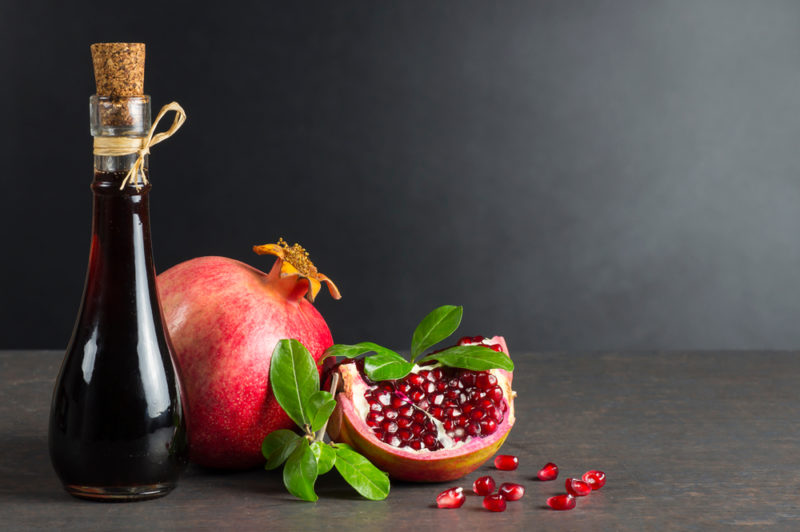 A full pomegranate, a pomegranate section, and a bottle of pomegranate juice on a black table against a black background