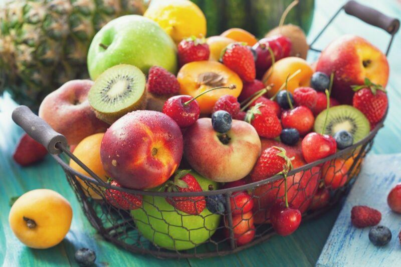A wire basket with a variety of fresh fruits, including kiwis, peaches, and apples